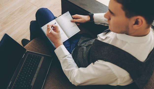 Ritratto di vista superiore di un uomo d'affari caucasico che pianifica la sua giornata scrivendo note in un libro e utilizzando un computer
