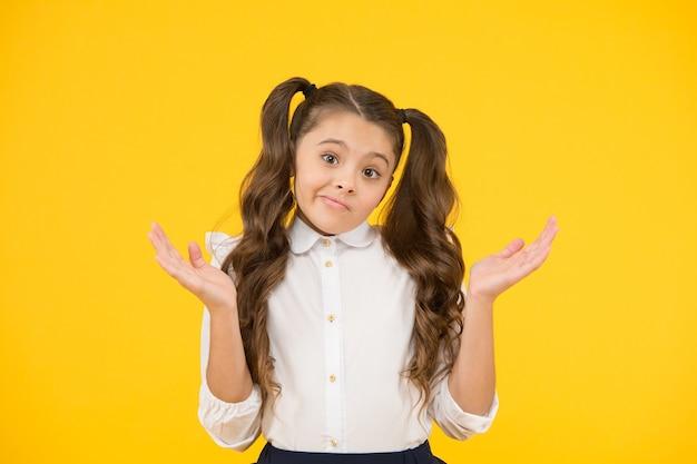 Ups. l'istruzione prima di tutto. piccolo bambino che fa un gesto impotente con le mani su sfondo giallo. ricevere la scuola dell'obbligo. concetto di educazione. un ottimo posto per l'istruzione.