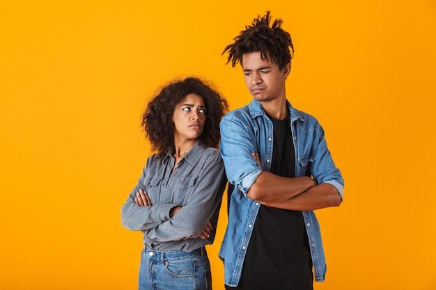 Sconvolto coppia africana in piedi isolato, schiena contro schiena