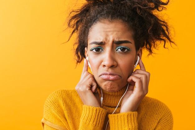 Donna africana sconvolta che indossa un maglione in piedi isolato, ascoltando musica con gli auricolari