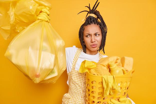 La donna afroamericana sconvolta guarda con avversione al sacco della spazzatura