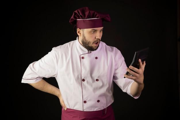 Sconvolto stupito giovane chef barbuto in uniforme guardando la calcolatrice
