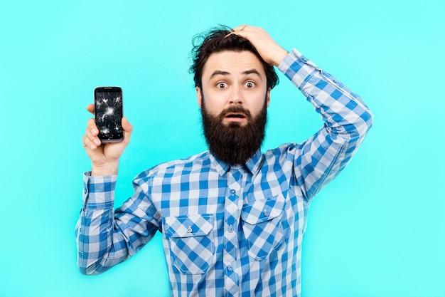 Uomo barbuto sconvolto in perdita con telefoni cellulari rotti su sfondo blu, servizio di ricerca gsm