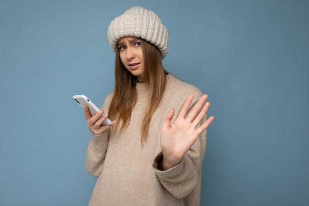 Sconvolto bella giovane donna bionda che indossa un maglione caldo beige elegante e beige caldo inverno lavorato a maglia
