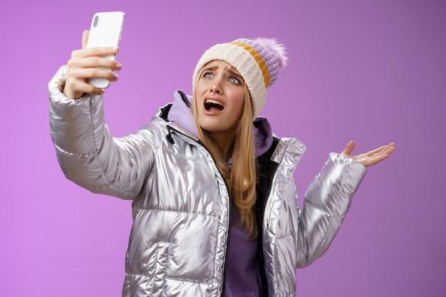 Ragazza bionda sconvolta e piagnucolosa che si lamenta non riesce a trovare l'angolo retto per scattare un selfie con belle visite turistiche durante le vacanze in viaggio all'estero urlando smartphone rivolto da parte, sfondo viola.