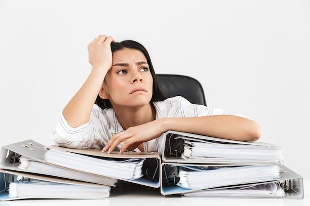Sconvolto bruna imprenditrice lavorando e seduto in ufficio con il mazzo di cartelle di carta sul tavolo isolato sopra il muro bianco
