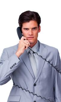 L'uomo d'affari turbato si aggroviglia nei cavi del telefono