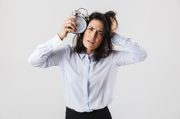 Donna di affari sconvolta elegantemente vestita in piedi isolato sul muro bianco, mostrando la sveglia
