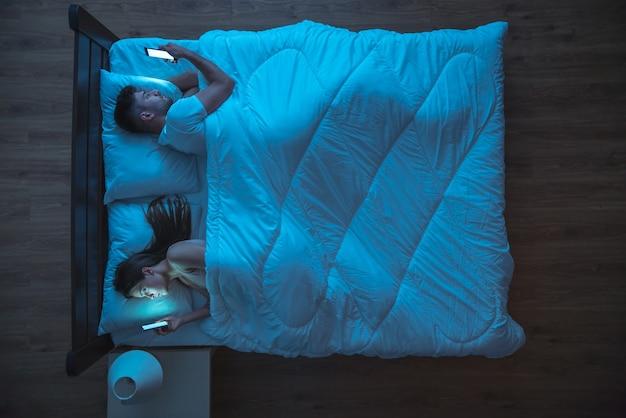 La coppia sconvolta con il telefono si trova sul letto. notte. vista dall'alto