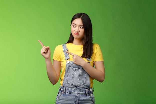 Sconvolto carino studentessa asiatica tirando la faccia rammarico vergogna peccato manca buone possibilità acquistare prodotto vendita ...