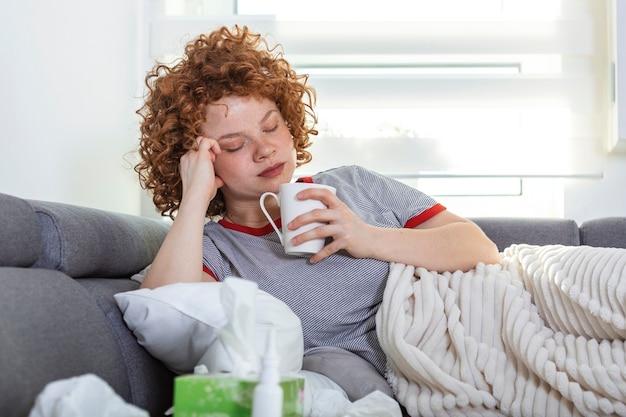 Sconvolto depresso giovane donna sdraiata sul divano sensazione di forte emicrania mal di testa, triste stanco sonnolento adolescente esausta ragazza che riposa cercando di dormire dopo tensione nervosa e stress, concetto di sonnolenza