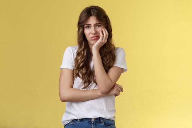 Sconvolto afflitto carino deluso bella ragazza sentirsi sola rammaricarsi occasione mancata sospirando dolore tristezza sguardo macchina fotografica apatico indifferente viso magro palmo accigliato geloso sfondo giallo.