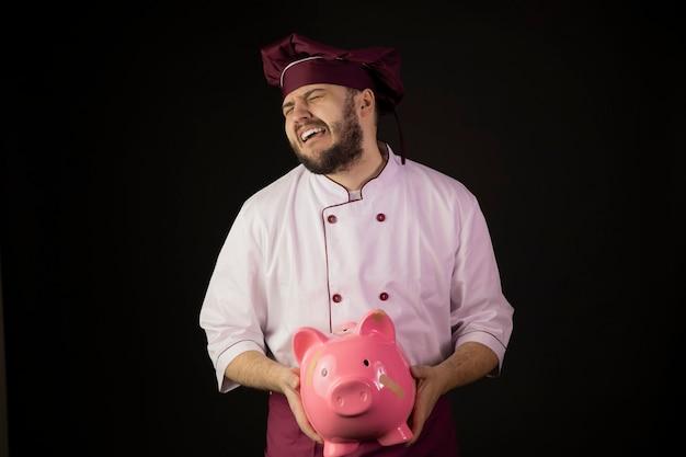 Il giovane chef barbuto angosciato sconvolto in uniforme grida che tiene il salvadanaio incollato