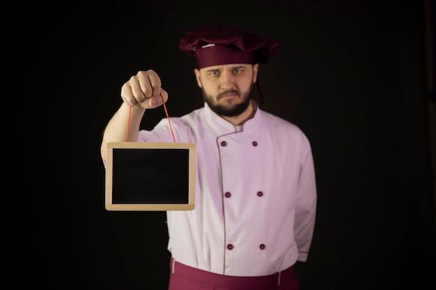 Il giovane chef maschio barbuto afflitto sconvolto in uniforme mostra la lavagna in bianco