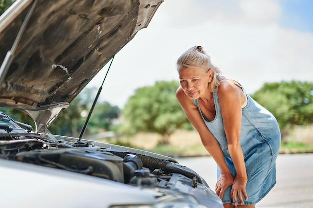 Donna adulta del conducente sconvolta davanti all'incidente di collisione dell'automobile rotta dell'automobile nella strada della città