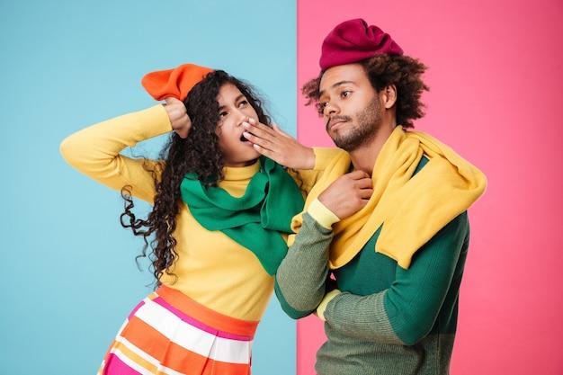 Sconvolto esausto afroamericano giovane coppia in cappelli e sciarpe in piedi e sbadigli