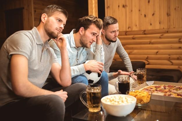 Gli amici sconvolti guardano una partita di calcio vicino al tavolo con un cibo