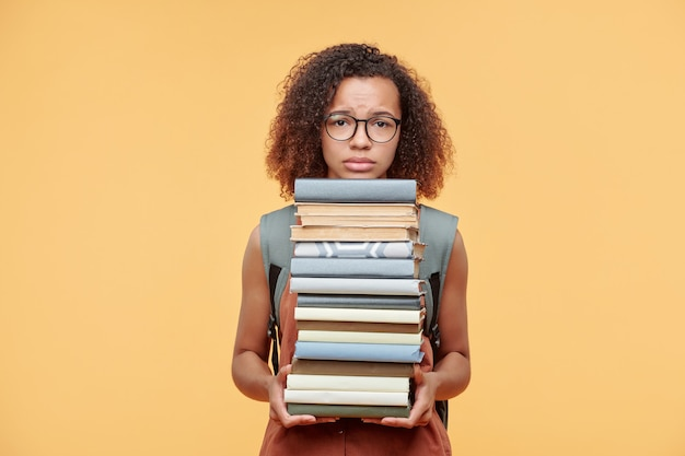 Sconvolto accigliata ragazza afro-americana con i capelli ricci tenendo una pila di libri su sfondo giallo, tempo di prepararsi per il concetto di esame