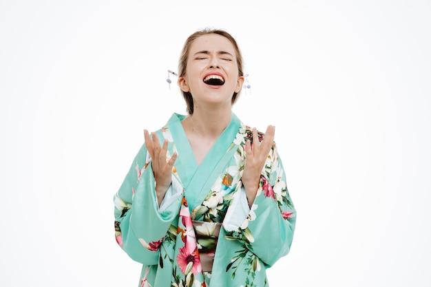 Giovane donna geisha sconvolta e frustrata nel tradizionale kimono giapponese che urla e grida alzando le braccia in piedi sul muro bianco