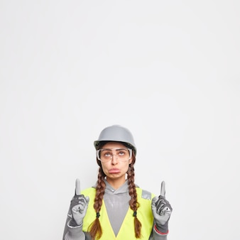 L'ingegnere donna cupa sconvolta visita il cantiere indossando il casco protettivo e l'uniforme di sicurezza dimostra i lavori di progetto di costruzione nei punti di sfera dell'industria sopra il muro bianco.