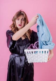 Casalinga turbata che giudica un canestro dei vestiti pronto per la lavanderia isolata sulla parete rosa