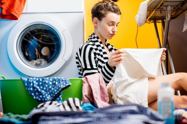 Casalinga sconvolta che guarda i vestiti sporchi seduta vicino alla lavatrice a casa