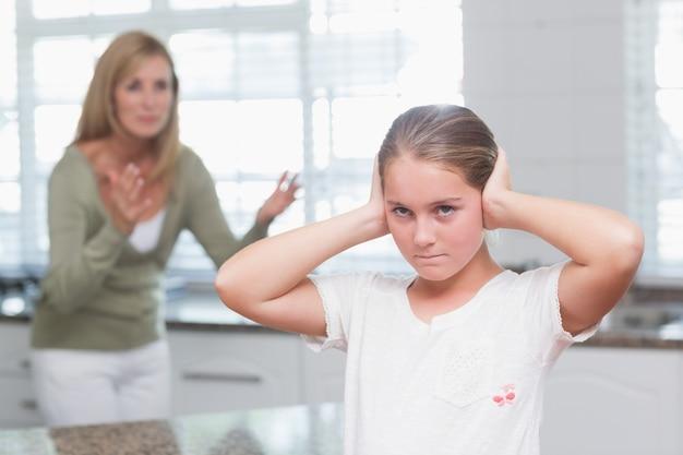 Bambina sconvolta che copre le sue orecchie mentre sua madre che grida