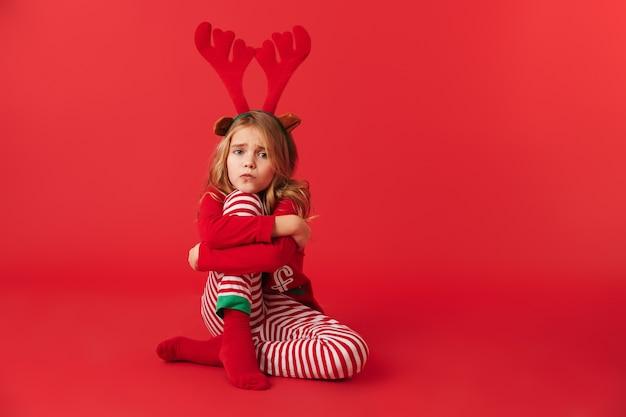 Bambina turbata che indossa la seduta del costume della renna di natale isolata