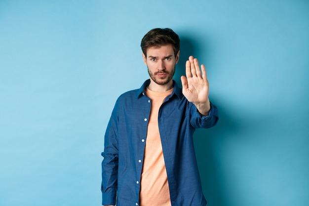 Uomo sconvolto che aggrotta le sopracciglia e chiede di fermarsi, allunga la mano per proibire o non essere d'accordo con qualcosa di brutto, in piedi su sfondo blu.