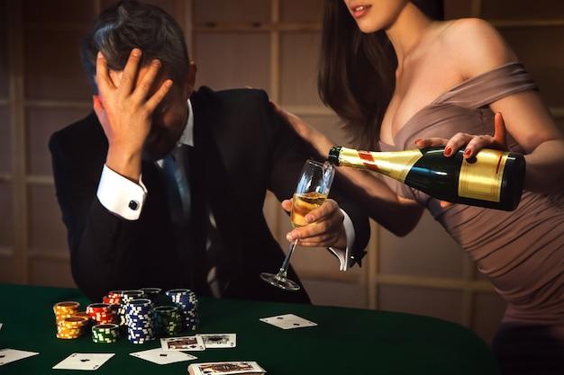 Uomo sconvolto perso a poker e una cameriera in un vestito con un profondo dekolte versa champagne in un bicchiere. a seconda del concetto di gioco d'azzardo e casinò