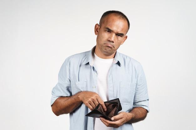 Uomo maturo turbato che tiene e che guarda dentro il suo portafoglio vuoto su fondo bianco. crisi finanziaria, fallimento, niente soldi, cattiva economia concetto.