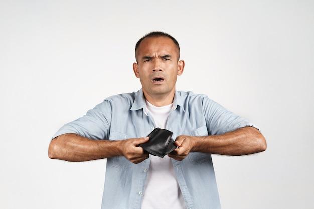 Uomo maturo turbato che tiene e capovolto il suo portafoglio vuoto su fondo bianco. crisi finanziaria, fallimento, niente soldi, cattiva economia concetto.
