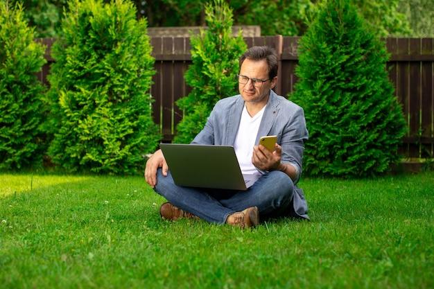 Uomo d'affari di mezza età sconvolto lavora con laptop e telefono cellulare all'aperto, si siede sull'erba, impiegato maschio triste ha perso il lavoro, cerca posti di lavoro, l'uomo ha problemi con affari privati, copia spazio