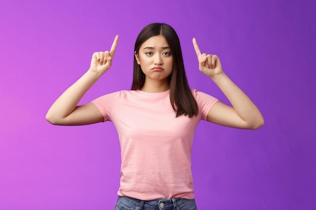 Sconvolta lunatica ragazza asiatica triste sembra gelosa, imbronciata angosciata, rivolta verso l'alto indicando le dita indice in alto pubblicità rammarico per la possibilità, in piedi deluso sfondo viola scontento