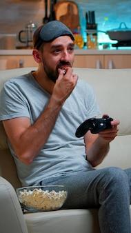 Sconvolto giocatore professionista seduto sul divano e giocando ai videogiochi di calcio
