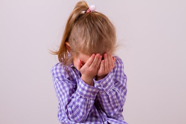 Bambino problema sconvolto con la testa tra le mani