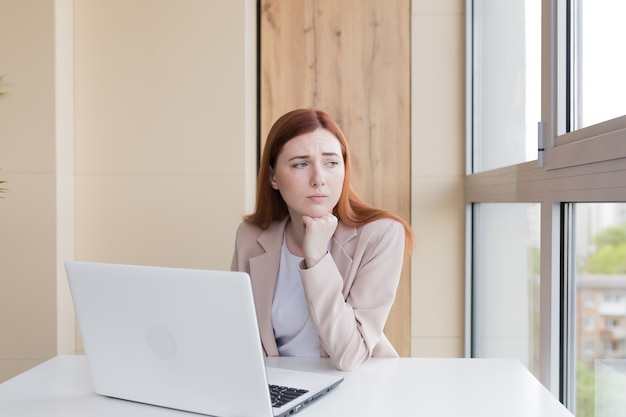 Donna d'affari dai capelli rossi sconvolta che lavora al computer seduta in ufficio