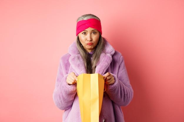 Una donna asiatica anziana sconvolta apre la borsa della spesa e guarda triste la telecamera, in piedi su sfondo rosa