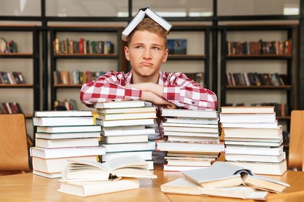 Ragazzo adolescente sconvolto seduto in biblioteca