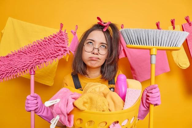 Una donna asiatica stanca e sconvolta indossa guanti di lattice e occhiali tiene mop e scopa