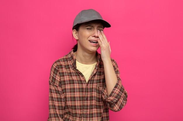 Sconvolto infelice giovane donna delle pulizie in abiti casual e berretto che piange forte strofinando gli occhi in piedi sul muro rosa