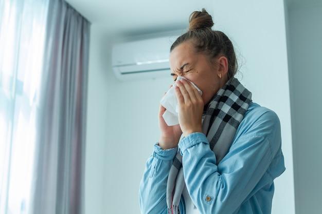 La donna turbata ha preso un raffreddore dal condizionatore d'aria e starnutiva