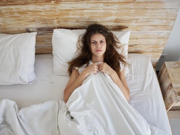 La donna sconvolta giace a letto sotto le coperte vista dall'alto del mattino