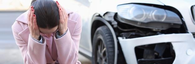 Una donna sconvolta si siede con la testa in giù accanto a incidenti stradali automobilistici sviluppati e