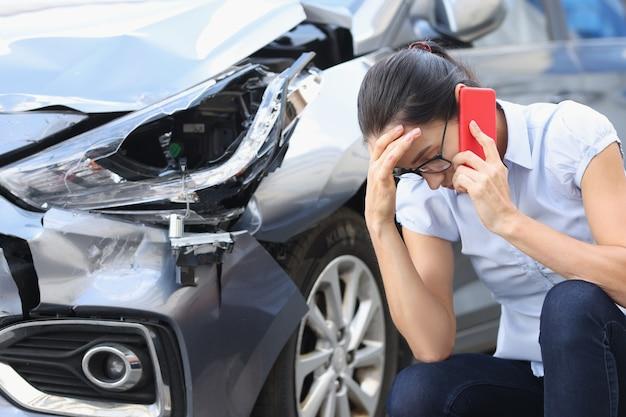 Donna sconvolta che parla al telefono sullo sfondo di un'auto rotta che chiama l'agente assicurativo dopo l'auto