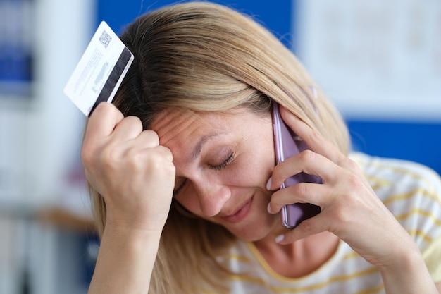 Donna sconvolta che parla al telefono e tiene in mano truffatori telefonici con carta di credito di plastica e prelievi di carte