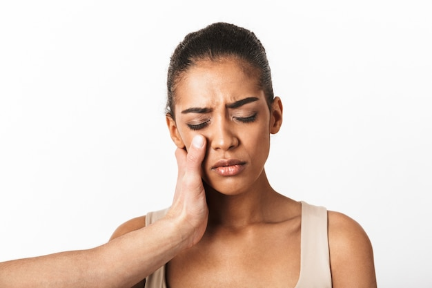 Sconvolto giovane donna africana che piange con la mano dell'uomo sul viso isolato su bianco