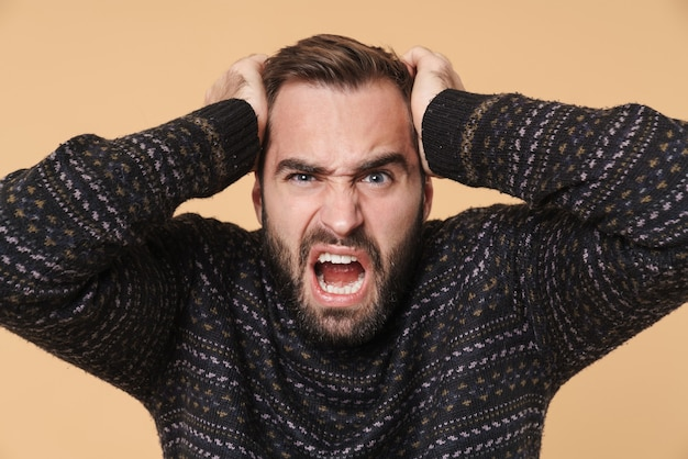 Sconvolto giovane uomo barbuto che indossa un maglione caldo in piedi isolato su un muro beige, soffre di mal di testa, urla