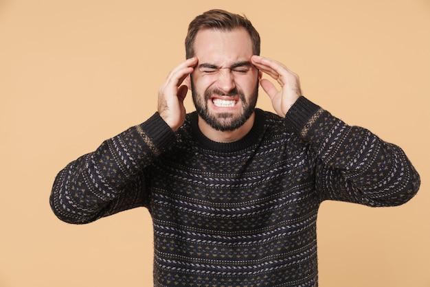 Sconvolto giovane uomo barbuto che indossa un maglione caldo in piedi isolato su un muro beige, che soffre di mal di testa