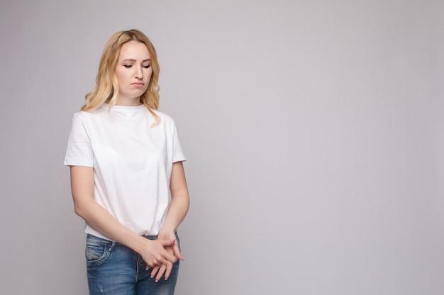 Giovane bella donna turbata che sta con le mani attraversate isolate al fondo bianco dello studio